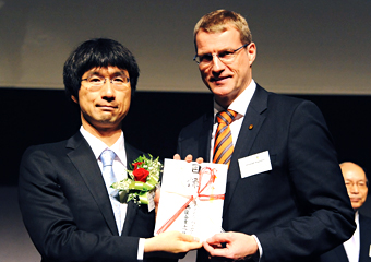 Kawano receiving the award certificate from a representative of the sponsoring companies