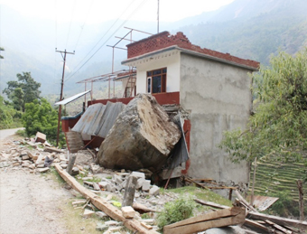 Massive rock dislodged from hill coming to rest against reinforced concrete building