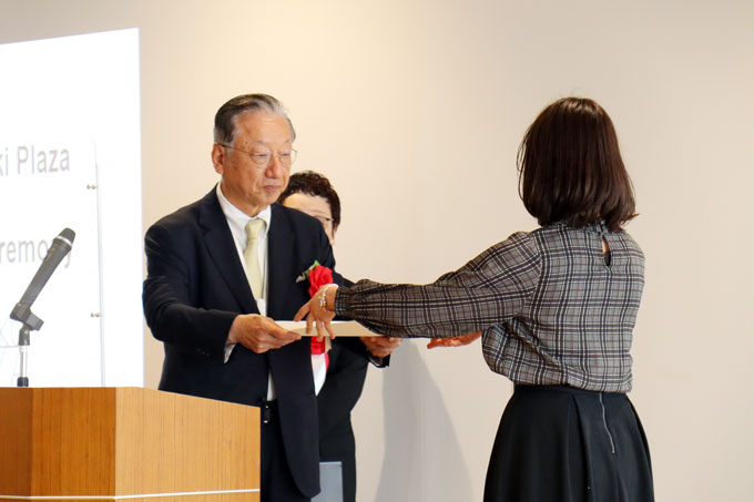 Alumnus Taki (left) presenting personal message to TPG leader Yanagase
