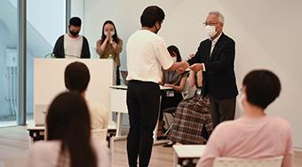 EVP Mizumoto (standing on right) appointing Student Ambassador