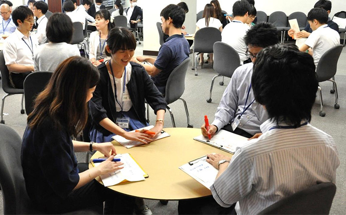 Staff members in groups of four around entakun, round cardboard tables used for brainstorming and discussion