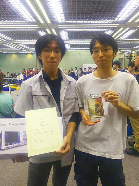 Chubachi (left) with certificate and prize, Suzuki holding winners' plaque
