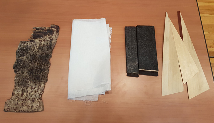 Tools for urushi painting: (From right) bamboo scraper, urushi brush, hemp cloth, and a particle from an old paint layer