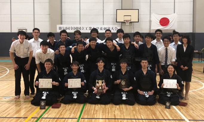 Ito (front row, third from left), Saito (front row, far left), and Kitahara (front row, far right) posing with other Kendo Club members after victory