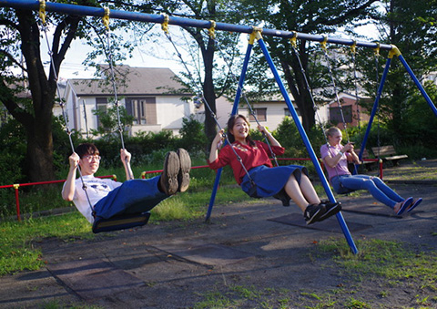 Participants enjoying the swings at the local park