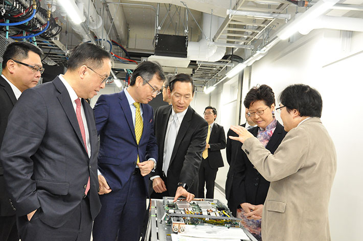 Aoki (far right) briefs Lam (second from right) on the TSUBAME 3.0 supercomputer
