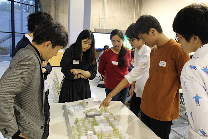 Students examining Taki Plaza model with architects