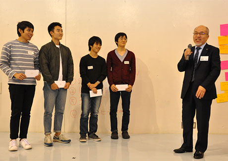 Gurunavi, Inc. Executive Vice President Hisao Iizuka (right) congratulating Team √3 for earning the Gurunavi Award