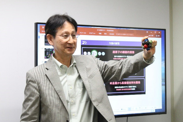 Professor Yamamoto explaining with a model of a one-nanometer clusters