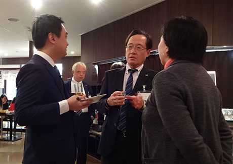 Masu (center) talking with attendee